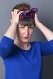 Grumpy trendy woman adjusting her scarf for fashionable hairstyle Royalty Free Stock Images