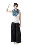 Grumpy trendy woman in wide-leg pants and neckerchief with thumbs down Stock Image