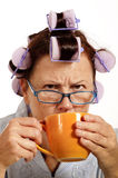 Grumpy Woman In Curlers Drinking Coffee In The Morning Royalty Free Stock Images