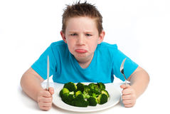 Grumpy young boy not happy about eating broccoli. royalty free stock images