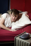 Grumpy young man waking up. To his alarm clock Royalty Free Stock Photography