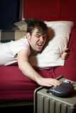 Grumpy young man waking up. And turning his alarm clock off Stock Photo