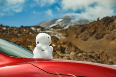 Grund av vulkan Teide Snögubbe på på huven av den röda bilen Peack av Teide med vita snöfläckar som täckas delvis av molnen royaltyfri fotografi