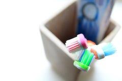Grund DOF sköt av tre tandborstar och tandkräm i en leratorktumlare i morgonljuset Royaltyfri Bild