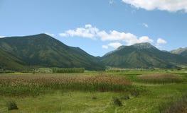 Grund flod med stora berg som omger den Royaltyfri Bild