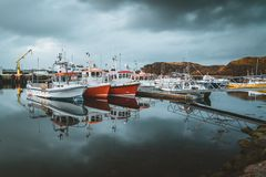 Grundarfjordur, Iceland - 03 January 2019: Harbor with motionless boats during the twilight of the afternoon, Kirkjufell. Volcanic mountain in the background royalty free stock photos
