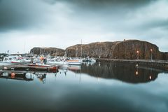 Grundarfjordur, Iceland - 03 January 2019: Harbor with motionless boats during the twilight of the afternoon, Kirkjufell. Volcanic mountain in the background stock photos