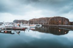 Grundarfjordur, Iceland - 03 January 2019: Harbor with motionless boats during the twilight of the afternoon, Kirkjufell. Volcanic mountain in the background stock images