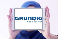 Grundig company logo. Logo of Grundig company on samsung tablet holded by arab muslim woman. Grundig is a German manufacturer of consumer electronics, domestic stock images
