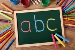 Grundläggande läsning för abc och handstil, svart tavla, skolaskrivbord Royaltyfria Bilder