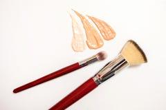Grundlagencremetropfen und Abstriche von verschiedenen Schatten für verschiedene Hautarten mit Bürsten für Anwendung und Schattie lizenzfreies stockbild