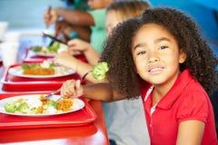 Grundlegende Schüler, die das gesunde Mittagessen in der Cafeteria genießen Lizenzfreie Stockfotografie