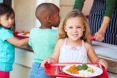Grundlegende Schüler, die das gesunde Mittagessen in der Cafeteria sammeln stockfotografie