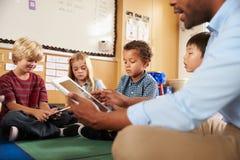 Grundlegende Schulklasse, die queresmit beinen versehenes unter Verwendung der Tabletten sitzt stockfotografie