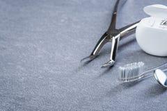 Grundlegende zahnmedizinische Werkzeuge, Glasschlacke und Bürste auf grauer Oberfläche Stockfoto