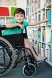 Grundlegender behinderter Junge, der Bücher in der Bibliothek sucht Lizenzfreie Stockbilder