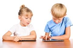 Grundlegender Junge und Mädchen am Tisch mit Auflagen stockfoto
