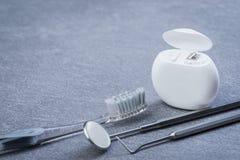 Grundläggande tand- hjälpmedel, floss och borsten på grå färger ytbehandlar Arkivbild