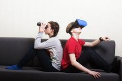 Grundlig ung flicka se de binokulära och för pojke bärande för virtuell verklighet 3D exponeringsglasen som sitter på soffan Royaltyfri Foto