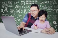 Grundschüler, der mit Tutor in der Klasse lernt stockbild