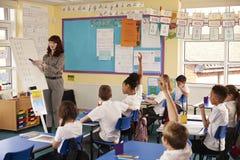 Grundschullehrer, der eine Flip-Chart in einer Lektion verwendet stockbilder