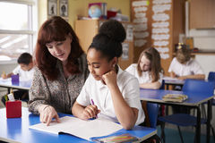 Grundschullehrer, der einem Schulmädchen an ihrem Schreibtisch hilft lizenzfreie stockfotos