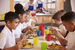 Grundskola för barn mellan 5 och 11 år lurar att äta på en tabell i skolakafeteria Arkivbild