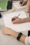 Grundskola för barn mellan 5 och 11 år lurar handstil med blyertspennor på deras skrivbord, slut upp Royaltyfri Bild