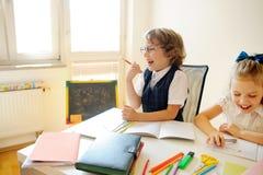 Grundskola för barn mellan 5 och 11 årelever sitter på det samma skrivbordet Arkivbild