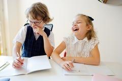 Grundskola för barn mellan 5 och 11 årelever sitter på det samma skrivbordet Arkivfoton