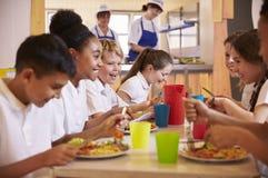 Grundskola för barn mellan 5 och 11 årungar på en tabell i skolakafeterian, slut upp Arkivbilder
