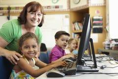 Grundskolaelev med läraren In Computer Class Royaltyfria Bilder