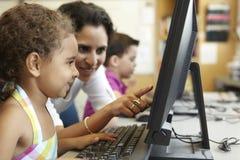 Grundskolaelev med läraren In Computer Class Royaltyfria Foton