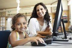 Grundskolaelev med läraren In Computer Class Royaltyfri Foto