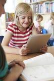 Grundskolaelev som använder den Digital minnestavlan i klassrum Arkivbilder
