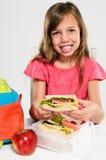Grundskolaflicka omkring som äter hennes matsäck Arkivfoto