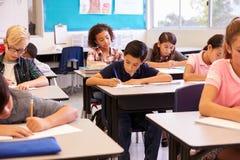 Grundskolan lurar arbete på deras skrivbord i ett klassrum royaltyfri fotografi