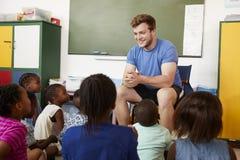 Grundskolan lurar sammanträde på golvet som lyssnar en lärare royaltyfri fotografi