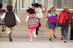 Grundskolan lurar spring in i skola, baksidasikt Arkivfoton