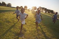 Grundskolan lurar spring till kameran i ett öppet fält arkivbilder