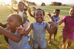 Grundskolan lurar spring till kameran utomhus, tätt upp arkivbild