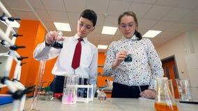 Grundskolastudenter som gör en kemi, experimenterar i ett vetenskapsklassrum stock video