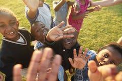 Grundskolaungar i ett fält ser upp på att vinka för kamera arkivfoton