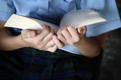 Grundskolaungen läser och rymmer bigbooken i hans hand royaltyfri fotografi