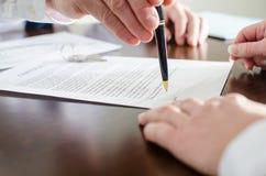 Grundstücksmakler, der den Unterzeichnungsort eines Vertrages zeigt Lizenzfreie Stockfotografie