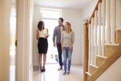Grundstücksmakler, der junge Paare um Eigentum für Verkauf zeigt stockfotografie