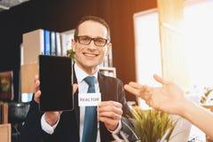 Grundstücksmakler, der am Schreibtisch im Büro sitzt Grundstücksmakler hält Tablette, Vater zeigt auf ihn lizenzfreie stockbilder