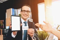 Grundstücksmakler, der am Schreibtisch im Büro sitzt Grundstücksmakler hält Tablette, Vater zeigt auf ihn lizenzfreie stockfotos