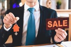 Grundstücksmakler, der am Schreibtisch im Büro sitzt Grundstücksmakler hält Verkaufszeichen und Ausschnittikone des Hauses stockbilder