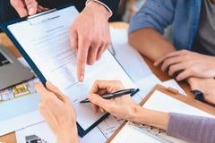 Grundstücksmakler, der am Schreibtisch im Büro sitzt Mutter unterzeichnet Vertrag für neue Wohnung stockfotografie